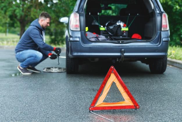 Triangle d'avertissement sur la route et l'homme change de roue de voiture