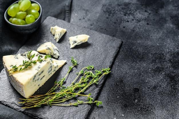 Triangle de fromage bleu avec des raisins sur une planche à découper