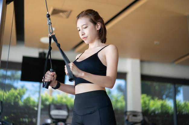 Triceps d'entraînement femme soulever des poids dans la salle de gym.