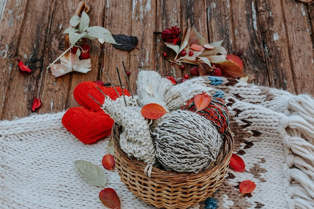 Tricot d'automne de vêtements chauds boules de laine d'aiguilles à tricoter coeurs tricotés choses faites maison avec...