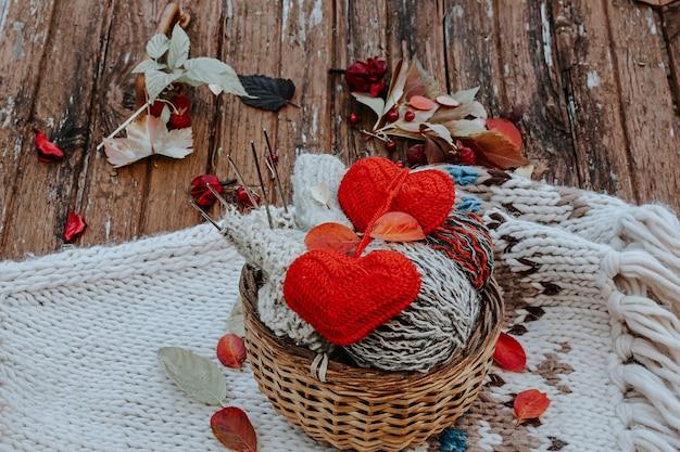 Tricot d'automne de vêtements chauds. boules de laine d'aiguilles à tricoter coeurs tricotés. des choses faites soi-même avec amour. idée de cadeaux faits à la main.