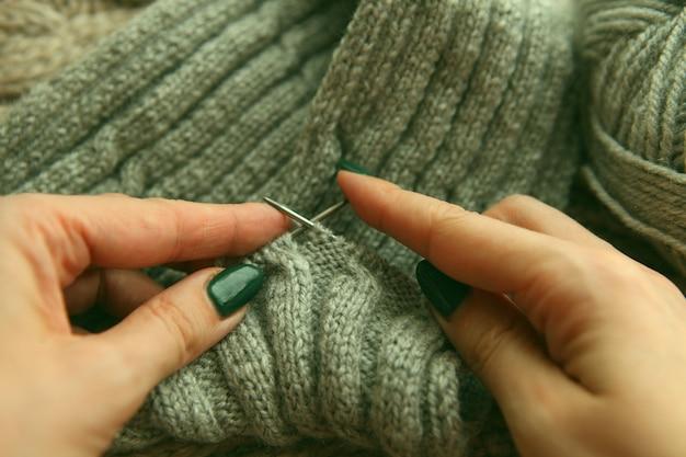 Tricot - mains de jeunes femmes utilisant des aiguilles à tricoter et un rouleau de laine grise. écharpe à tricoter mains femme