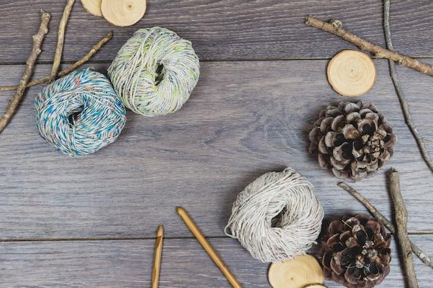 Tricotage de fournitures avec des branches et des cors de pin sur une table en bois