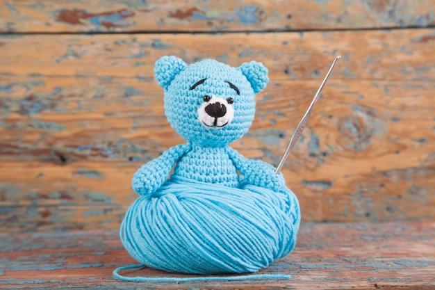 Tricoté petit ours sur un fond en bois ancien. jouet tricoté à la main. amigurumi
