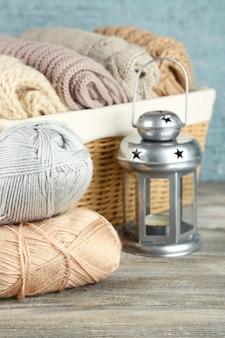 Tricoter des vêtements et du fil dans le panier, sur fond de bois