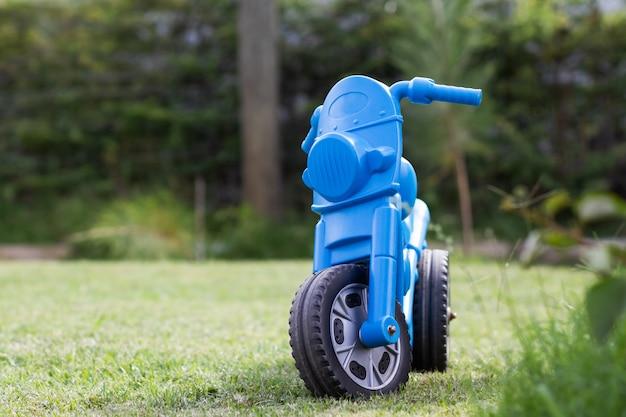 Tricycle pour enfants en plastique bleu abandonné dans le jardin.