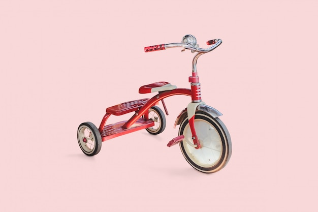 Tricycle vintage enfant rouge sur fond de couleur.