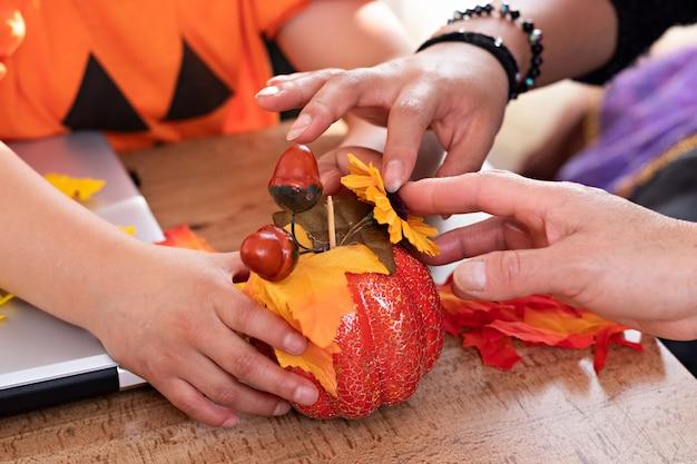 Un trio de mains accueillant une mini citrouille de décoration sur une table avec une décoration plus halloween
