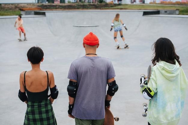 Trio de skateurs au repos regardant les autres s'essayer au skatepark. de derrière leur dos.