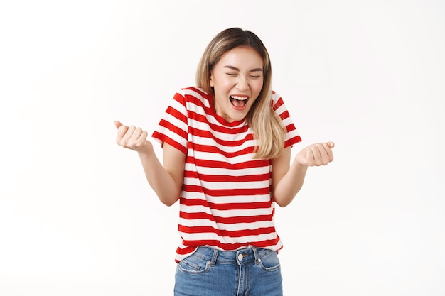 Triomphant joyeuse fille asiatique blonde fermer les yeux en criant positivement le bonheur avoir un accord réussi serrer les poings optimiste recevoir l'approbation gagner le prix atteindre l'objectif