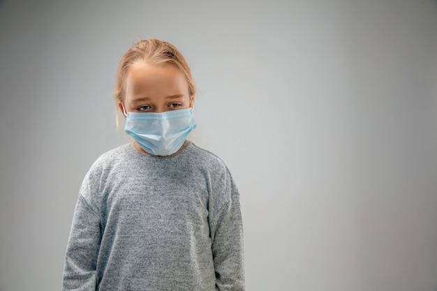 Triste avenir. petite fille caucasienne portant le masque de protection respiratoire contre la pollution de l'air et les particules de poussière dépassent les limites de sécurité. concept de soins de santé, d'environnement, d'écologie.