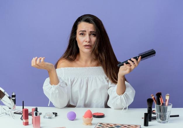 Triste belle fille est assise à table avec des outils de maquillage tenant un peigne à cheveux isolé sur un mur violet