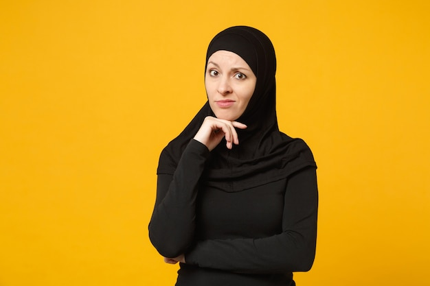 Triste bouleversée pleurant confuse jeune femme musulmane arabe en vêtements noirs hijab posant isolé sur mur jaune, portrait. concept de mode de vie de l'islam religieux.