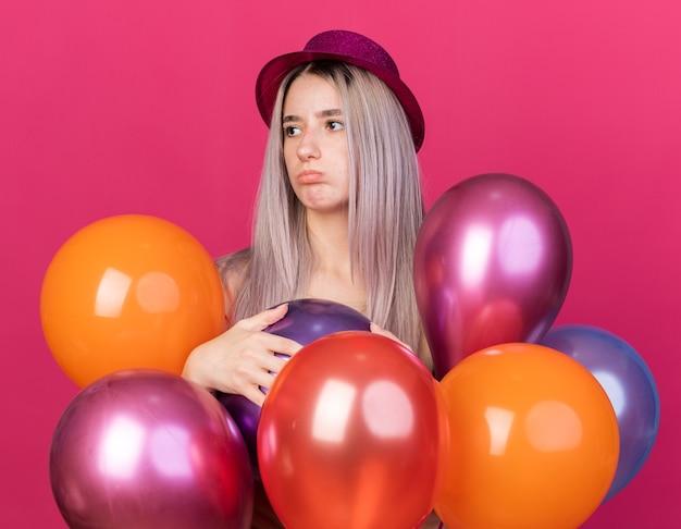 Triste côté jeune belle femme portant un chapeau de fête avec des appareils dentaires debout derrière des ballons isolés sur un mur rose