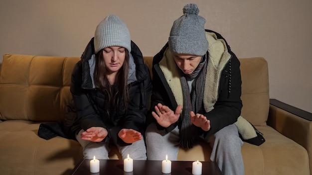 Triste couple gelé dans des vestes chaudes essaie de chauffer les paumes sur des bougies allumées assis sur un canapé dans une chambre froide sans chauffage central
