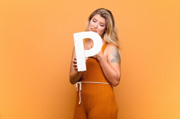 Triste, déprimé, malheureux, tenant la lettre p de l'alphabet pour former un mot ou une phrase.