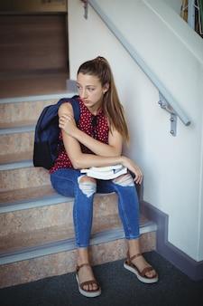 Triste écolière assise seule sur l'escalier