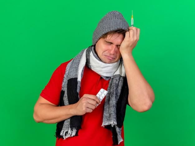 Triste et effrayé jeune bel homme malade blonde portant un chapeau d'hiver et une écharpe tenant un paquet de comprimés médicaux et une seringue touchant la tête avec les yeux fermés isolé sur fond vert avec espace de copie