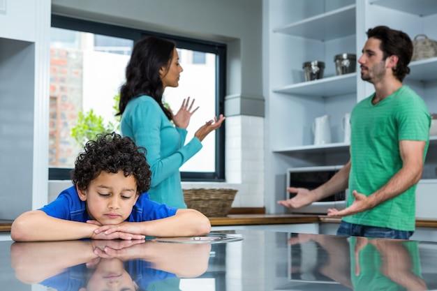 Triste enfant écoutant l'argument des parents