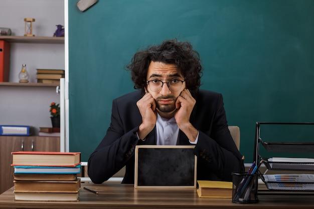 Triste enseignant portant des lunettes tenant un mini tableau noir assis à table avec des outils scolaires en classe