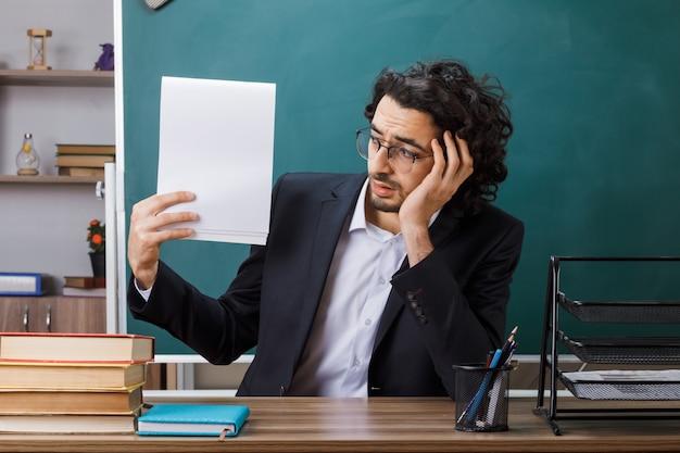 Triste enseignant portant des lunettes tenant et regardant le papier assis à table avec des outils scolaires en classe