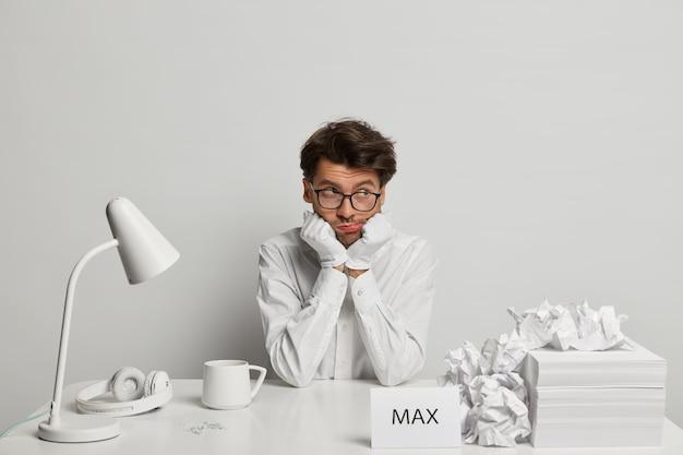 Triste étudiant masculin ennuyé en tenue de neige blanche, pense à la préparation aux examens