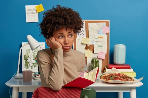 Triste étudiant universitaire réfléchi tient un cahier avec des notes colorées collantes à l'intérieur