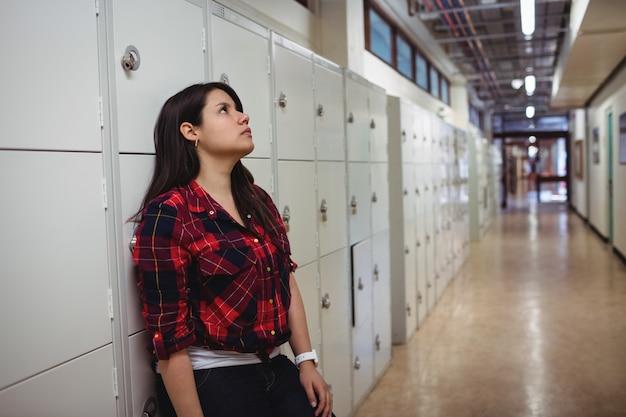Triste étudiante s'appuyant sur un casier