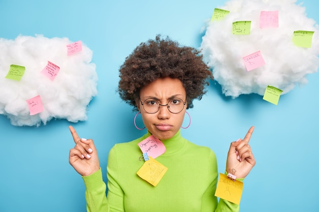 Triste femme afro-américaine frustrée point ci-dessus sur les nuages avec des notes autocollantes des tâches écrites à faire comme beaucoup de travail porte des lunettes rondes et un col roulé vert isolé sur un mur bleu