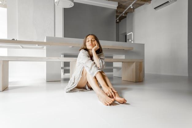 Triste femme assise déprimée seule à la maison