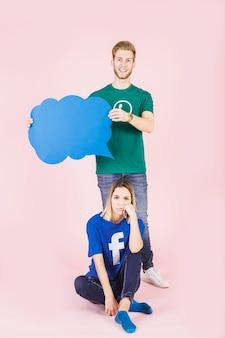 Triste femme assise devant un homme heureux tenant une bulle bleue vide