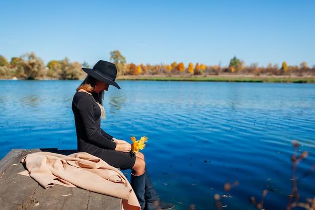Triste femme assise sur le quai de la rivière tenant des feuilles jaunes