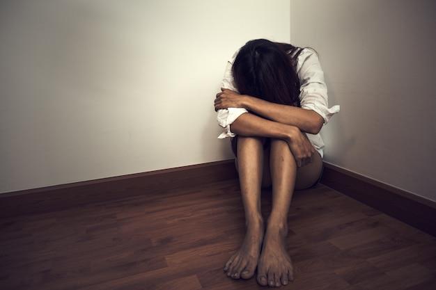 Triste femme assise seule dans une pièce vide