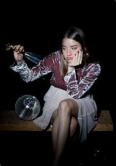 Triste femme assise avec un verre de champagne à la main