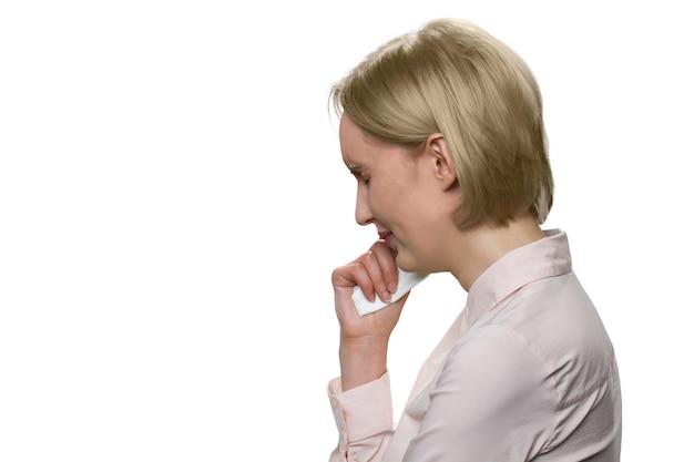 Triste femme blonde qui pleure s'est détournée sur un mur blanc