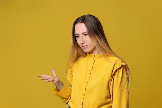 Triste femme insatisfaite sur fond jaune. émotions humaines, expressions faciales.