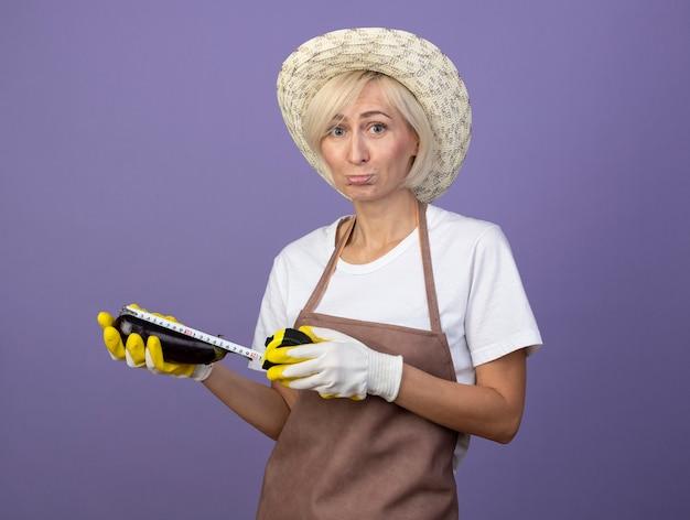 Triste femme jardinière blonde d'âge moyen en uniforme portant un chapeau et des gants de jardinage mesurant l'aubergine avec un mètre ruban