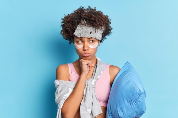 Triste femme malheureuse aux cheveux bouclés garde la main sous le menton offensé a la mauvaise humeur tient un oreiller habillé en pyjama des patchs de beauté sous les yeux pour rajeunir la peau
