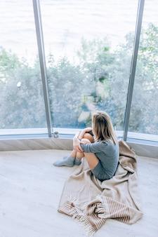 Triste femme mince assise sur un sol chaud dans une robe grise près de la grande fenêtre à la lumière et serrant ses genoux. ambiance d'automne, chaleur et confort.