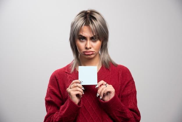 Triste femme tenant un bloc-notes sur fond gris.