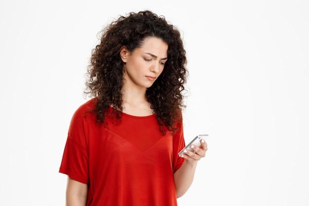 Triste fille bouclée bavardant sur son téléphone