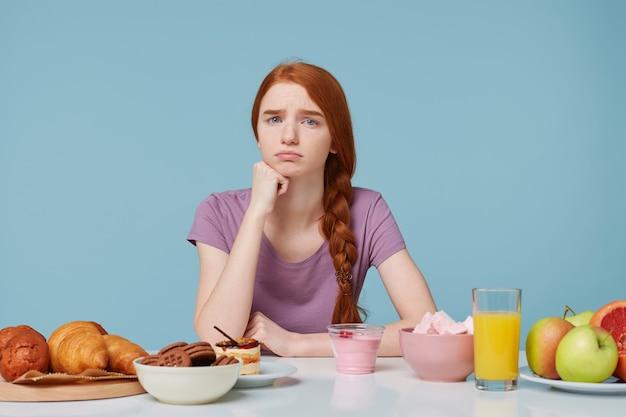 Triste fille rousse bouleversée à la caméra avec insatisfaction, pense à l'alimentation