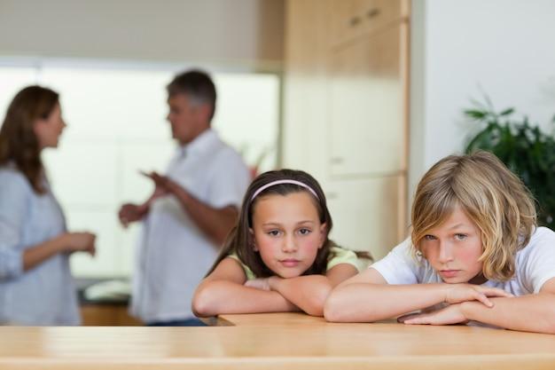 Triste frère et sœur regardant avec des parents qui se battent derrière eux