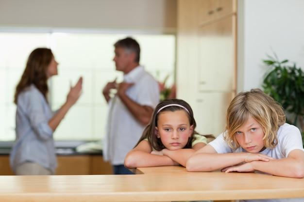 Triste frères et sœurs avec des parents qui se disputent derrière eux