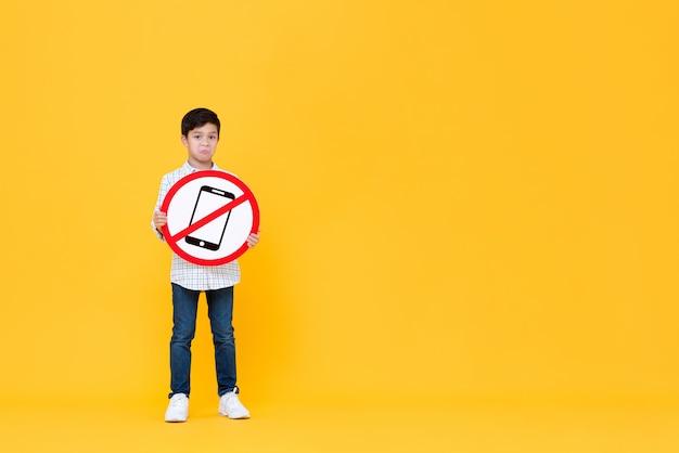 Triste garçon asiatique tenant la signalisation de téléphone portable interdit
