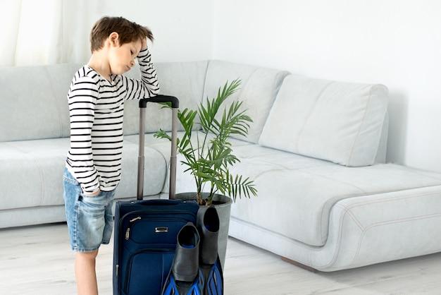 Triste garçon touristique avec une valise et des palmes reste à la maison