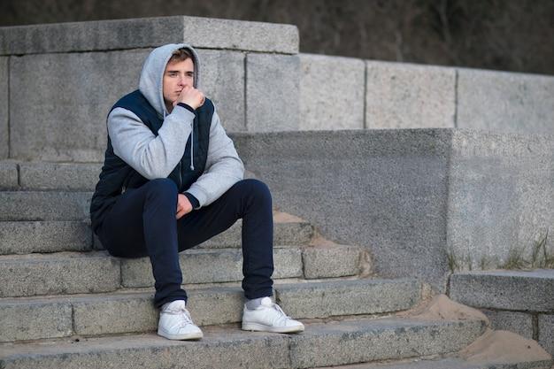 Triste gars déprimé, déprimé, jeune homme frustré solitaire assis dans les escaliers dans le capot, souffrant de mauvaise humeur, pensant aux problèmes futurs, regardant au loin. coeur brisé, concept d'échec.