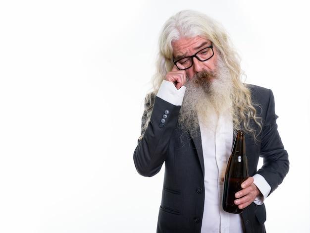 Triste homme d'affaires barbu senior tenant une bouteille de