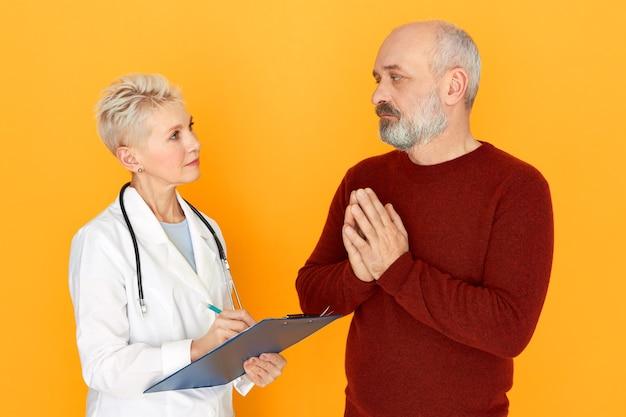 Triste homme âgé frustré avec barbe pressant les mains pour demander à sa femme médecin de le guérir d'une maladie respiratoire lors d'un examen physique, en parlant de symptômes.