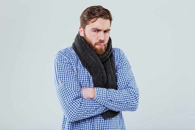Triste homme barbu malade en écharpe avec thermomètre dans sa bouche sur mur blanc
